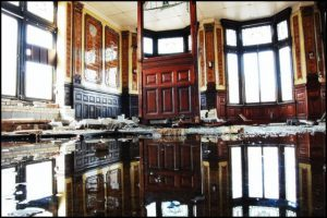 Picture of an old historical home with the floors flooded with water.