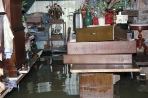 Picture of a house that has water flooding the first floor. The furniture is under water with items stacked to prevent further damage